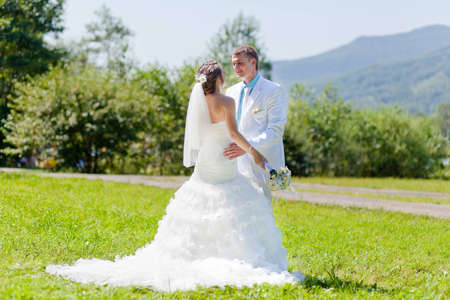 Bride and groom hugging tenderly at a green grass Stock Photo
