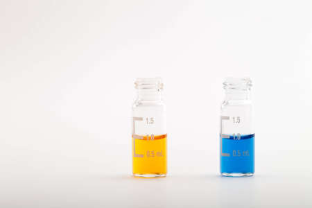 Two chromatographic glass vials filled each with one milliliter of color liquid  Isolated on white