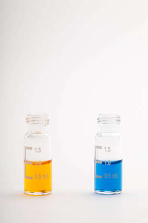 analytical chemistry: Two chromatographic glass vials filled each with one milliliter of color liquid  Isolated on white