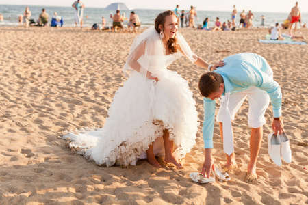 Groom helps the bride to take off her shoes at the crowded beach at sunset