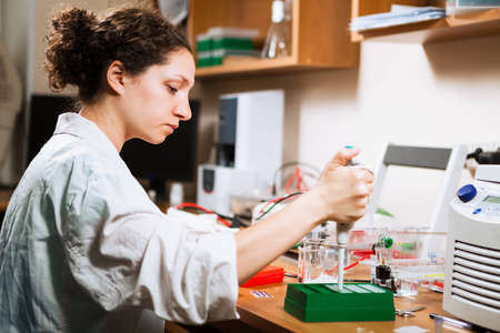 electrophoresis: Female researcher in a lab performs sample preparation for DNA electrophoresis making dots of ethidium bromide