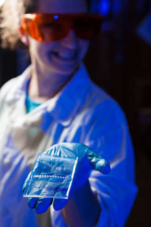electrophoresis: Female researcher in protective glasses holding in hand an agarose gel plate with results of DNA analysis Stock Photo