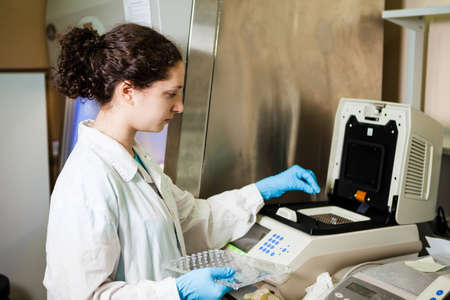 Female researcher loads DNA samples into PCR reactor photo