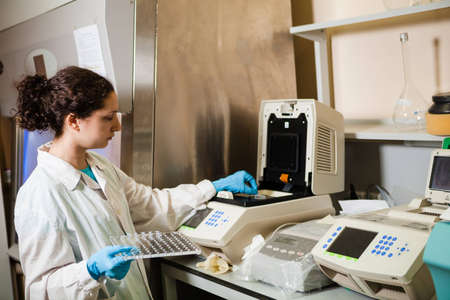 amplification: Female researcher loads DNA samples into PCR reactor