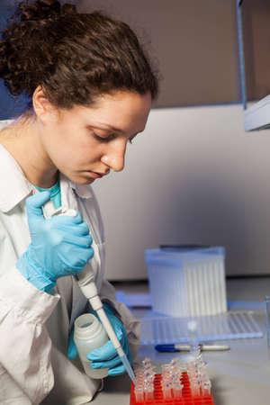 Female researcher making preparation of biological samples photo