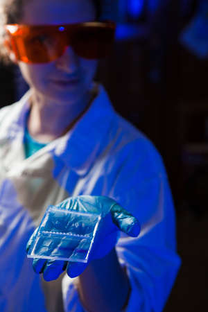 Female researcher in protective glasses holding in hand an agarose gel plate with results of DNA analysis photo