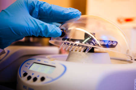 centrifuge: Loading samples to centrifuge for separation  Part of DNA extraction procedure Stock Photo
