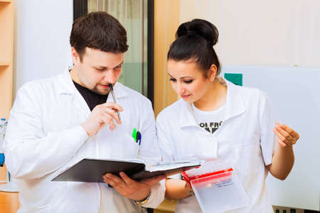Two scientists with lab journal discussing results of experiment Stock Photo - 13889068