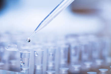 eppendorf: Pipette tip with a droplet over a rack of test tubes  Close up  Blue toning  Stock Photo