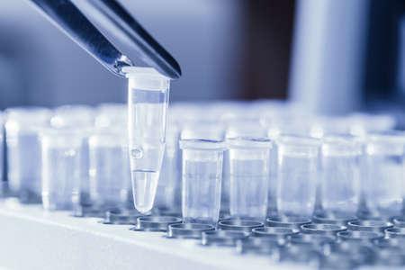 amplification: Close-up d'une pincette de chargement des tubes � essai avec de l'ADN pr�lev� pour la r�action en cha�ne par polym�rase image vir�e Bleu Banque d'images