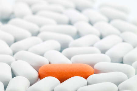 Individuality concept - Single orange pill between white ones Stock Photo
