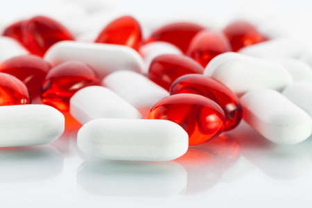 Extreme close-up view of vitamin pills  white tablets and red vitamin E capsules photo