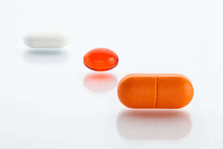 Extreme close-up view of three various pills  orange, red oil capsule and white one photo