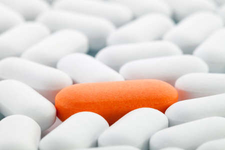 Individuality Concept: Single orange pill between white ones