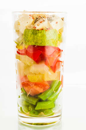 Vegetable verrine salad with young zucchini, tomatoes, paprika, beans, celery and sheep cheese photo