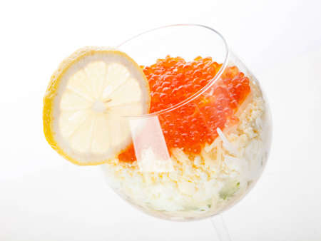 Cocktail salad with salmon, cucumber, cheese, egg and caviar, served in tall wineglass with a slice of lemon Stock Photo
