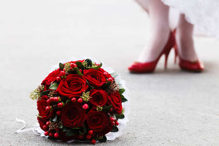Wedding bouquet of red roses and bride s feet in high-heeled red shoes behind