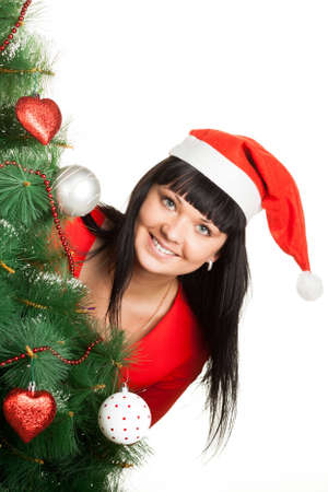 Attractive brunette in red Santa s cap looking out of Christmas tree photo