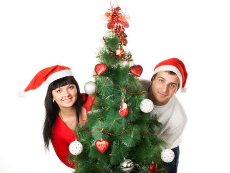 Family couple in red Santa s caps looking out of Christmas tree Stock Photo