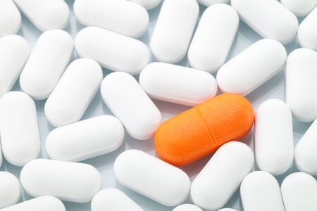 odd one out: Individuality Concept  Single orange pill between white ones Stock Photo