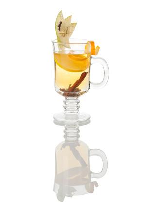 orange peel clove: tazza di vetro di grog ambra caldo con cannella, mela e fetta d'arancia, con la riflessione su bianco
