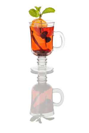 glass mug of hot red grog with cinnamon, raspberry, mint and slice of orange, with reflection over white