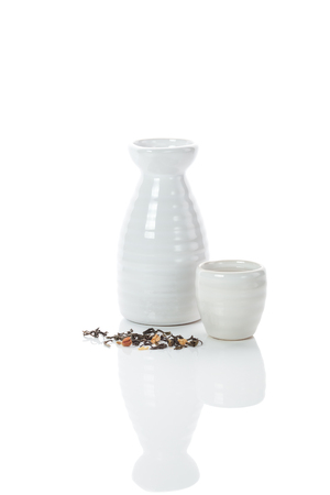 white porcelain traditional japanese jug and shot of sake with scattering tea leaves Stock Photo