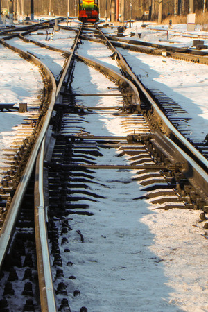 turnouts: rails in the sun in the snow with turnouts in the foreground Stock Photo