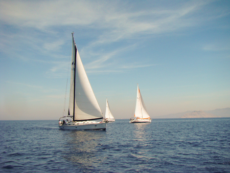 blu sky: three boats are sailing at low speed Stock Photo