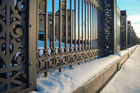 ironwork: fragment of forged metal fence on the foundation Stock Photo