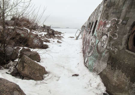 window graffiti: old concrete wall with windows near the rocks