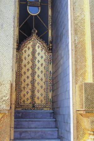 ornate door: ornate door with steps in a narrow passage