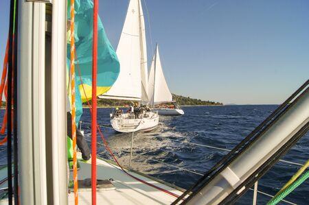 deportes nauticos: parte de la cubierta del yate con un mástil de metal y las velas