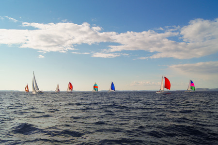 deportes nauticos: Yate con las velas de colores bajo un cielo azul