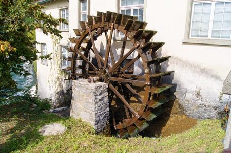 molino de agua: rueda de molino de agua entre la casa y el armario de la cocina Foto de archivo