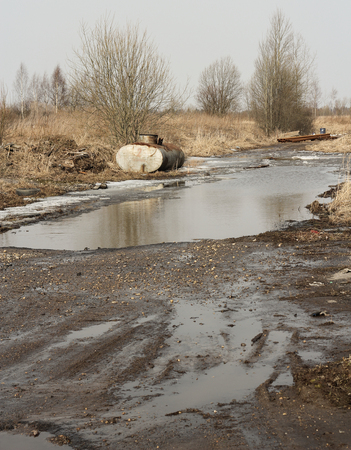 melted spring rural road with puddle and snow photo