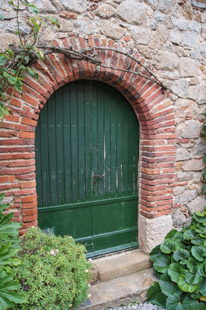 arched: arched green wooden door in a wall of stone Stock Photo