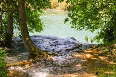 murmur: the flow of water flowing into the river from the shore Stock Photo