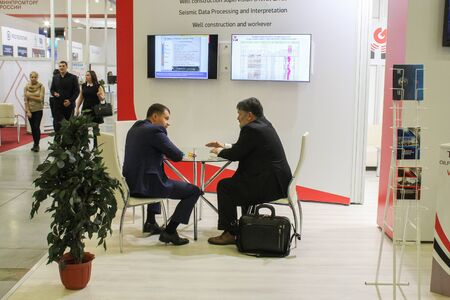 discussed: St. Petersburg, Russia - 8 October, 2015.Expo forum. International Gas Forum. Two men at a table that is actively discussed.
