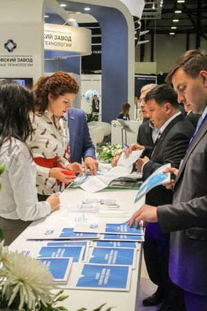 handouts: St. Petersburg, Russia - 6 October, 2015.Expo forum. International Gas Forum. Men interested in handouts lying at the front of the company.