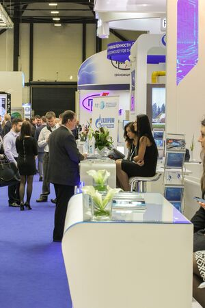 exhibition crowd: St. Petersburg, Russia - 7 October, 2015.Expo forum. International Gas Forum. The man is talking to two girls.