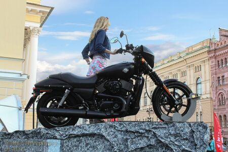 exhibition crowd: Girl posing with a motorcycle. St. Petersburg, Russia - 7 August, 2015. Bike Show Harley Davidson in St. Petersburg.