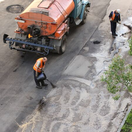 asphalting: Workers producing preparations. Leningrad region, Russia - 15 June, 2015. Landscaping and asphalting of yards. Editorial