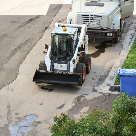 mini loader: Mini Loader for small works. Leningrad region, Russia - 15 June, 2015. Landscaping and asphalting of yards.