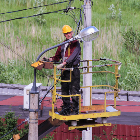 elevator operator: Electricians Managing basket aerial platforms. Editorial