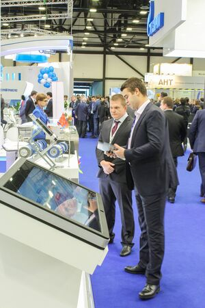 modern business: Two business man in front of a large monitor on the forum. St. Petersburg, Russia - 6 October, 2015.Expo forum. International Gas Forum. Editorial