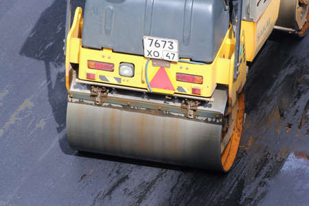 compacted: Road vehicle compacted asphalt. Leningrad region, Russia - 15 June, 2015. Landscaping and asphalting of yards. Editorial