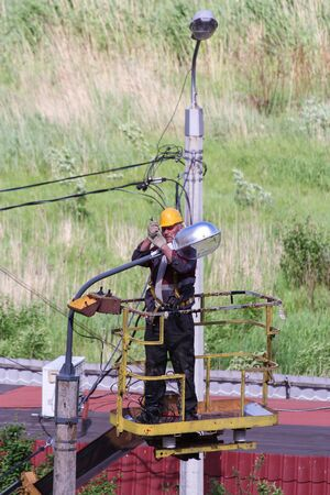 elevator operator: Electricians working with street lighting lanterns. Leningrad region, Russia - 15 June, 2015. Landscaping and asphalting of yards.