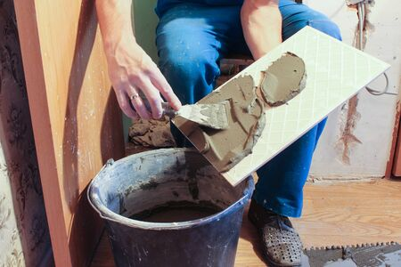 smearing: Smearing glue on the tile trowel.