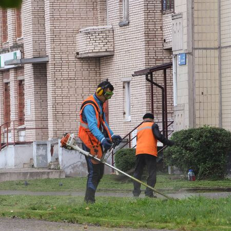 mowing grass: Worker mowing grass. Leningrad region, Russia - 15 June, 2015. Landscaping and asphalting of yards.